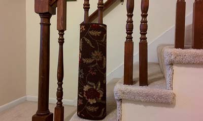 Flowered area rug wrapped around staircase spindle
